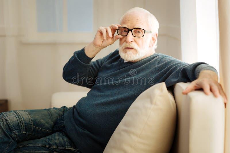 Starker bärtiger Mann, der seine Gläser berührt stockbild