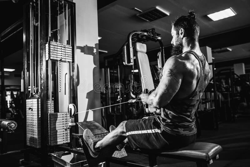 Starker Bodybuilder, der Schwergewichts- Übung für Rückseite auf Maschine tut stockfoto