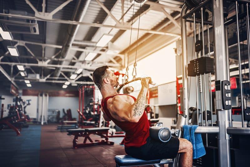 Starker Bodybuilder, der Schwergewichts- Übung für Rückseite auf Maschine tut lizenzfreies stockfoto