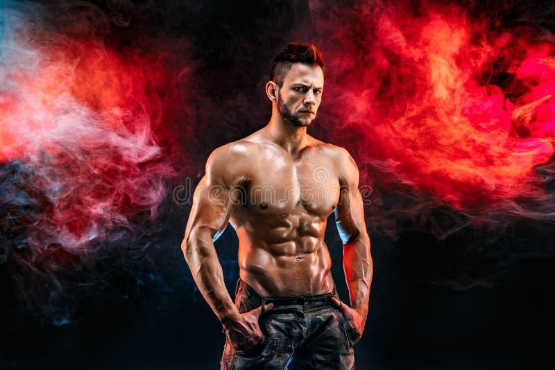 Starker Bodybuildermann in den Militärhosen mit perfekten ABS, Schultern, Bizeps, Trizeps, Kasten stockbilder