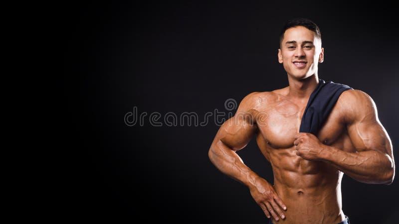 Starker Bodybuildermann, der mit der perfekter ABS, Pecs, Schultern, Bizeps, Trizeps und dem Kasten hält ein Tuch lächelt Auf stockfotos