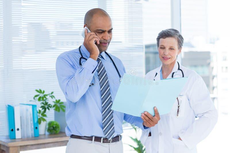 Starker Doktor, der seinem Kollegen Datei beim Nennen zeigt stockbilder