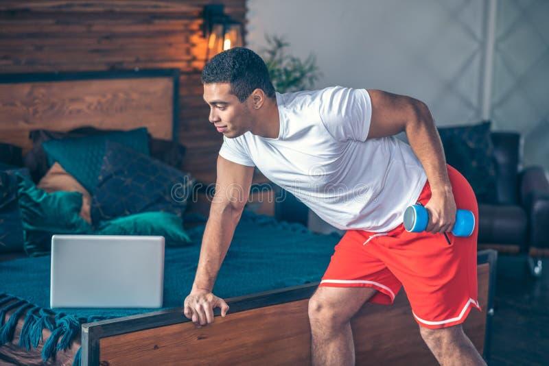 Starker dunkelhahaariger Mann in roten Hosen, der an seinen Biceps arbeitet stockfotografie