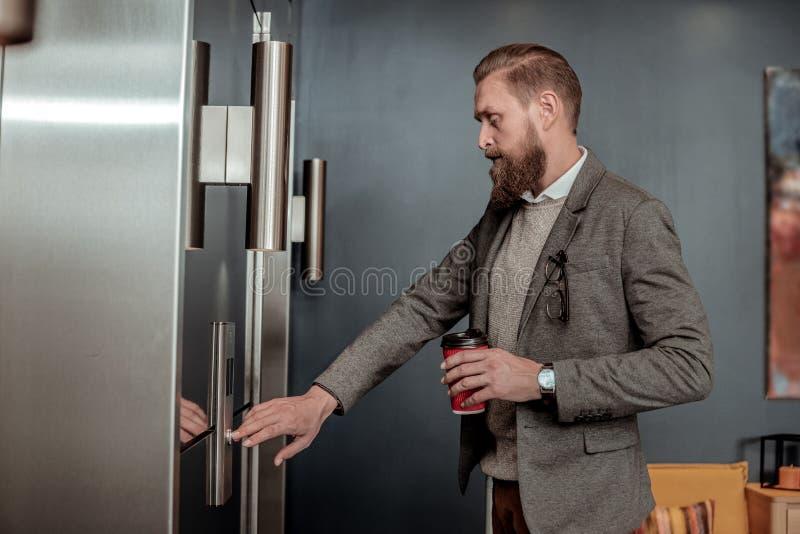 Starker Geschäftsmann, der den Knopf vom Aufzug betätigt lizenzfreies stockfoto
