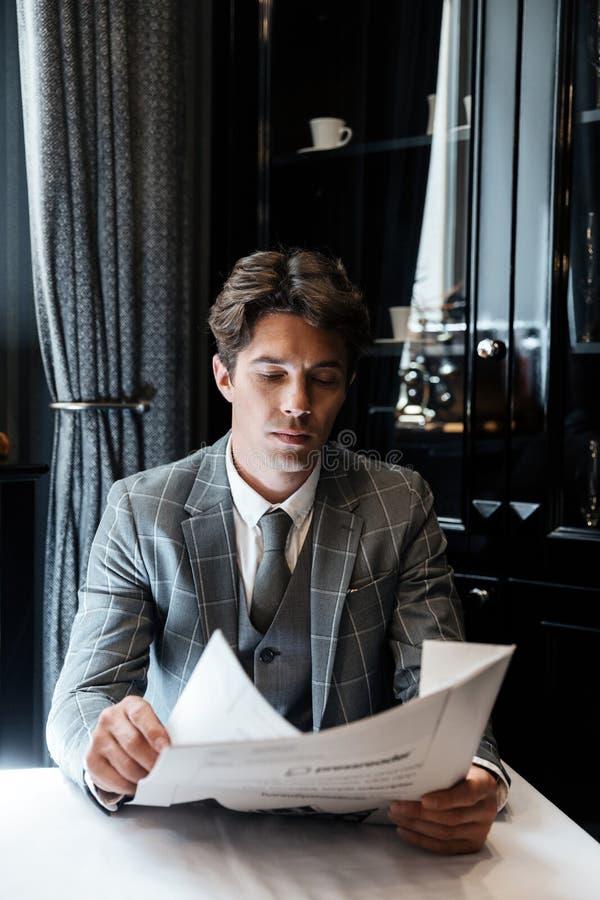 Starker Geschäftsmann in der Klage eine Zeitung lesend stockbilder