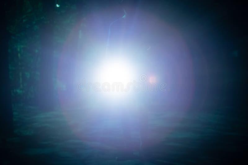starker Handlichtfackel-Strahlnanschlag in Ihrem Gesicht nachts stockfotografie