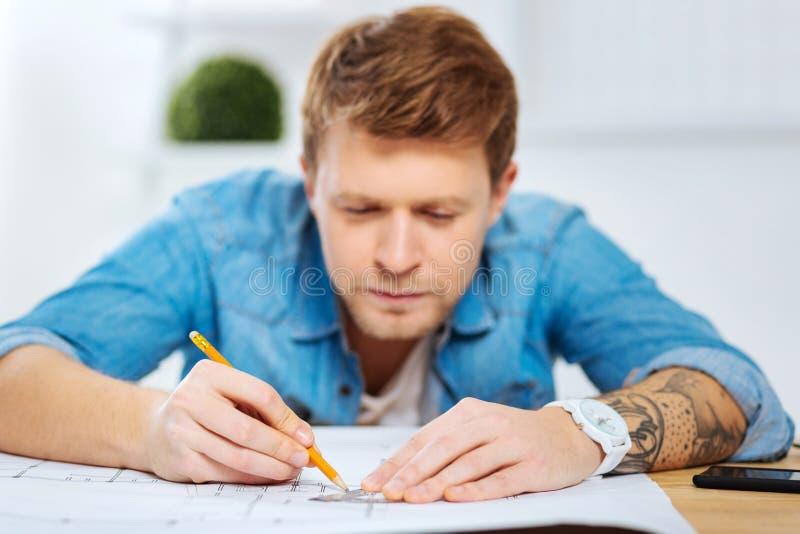 Starker Ingenieur, der vorsichtig schaut, während das Zeichnen zeichnet stockfotos