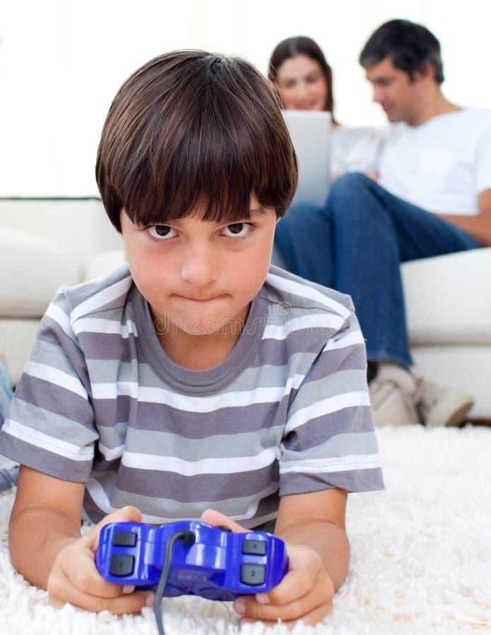 Starker Junge, der Videospiel auf einem Fußboden spielt lizenzfreie stockfotografie