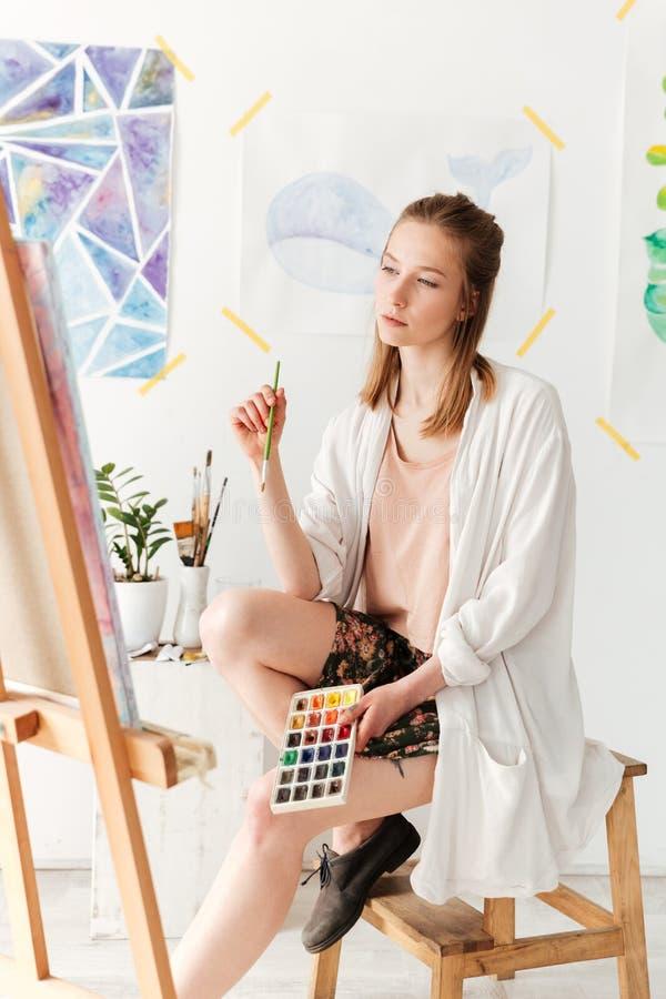 Starker junger kaukasischer Damenmaler am Arbeitsplatz stockfoto