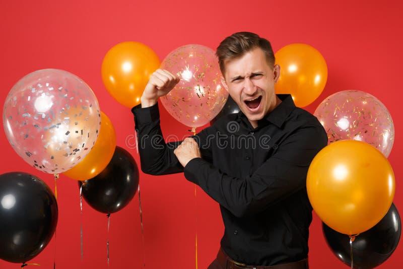 Starker junger Mann im klassischen Hemd, welches das Bizeps, schreiend auf hellen roten Hintergrundluftballonen zeigt St.-Valenti stockfotografie