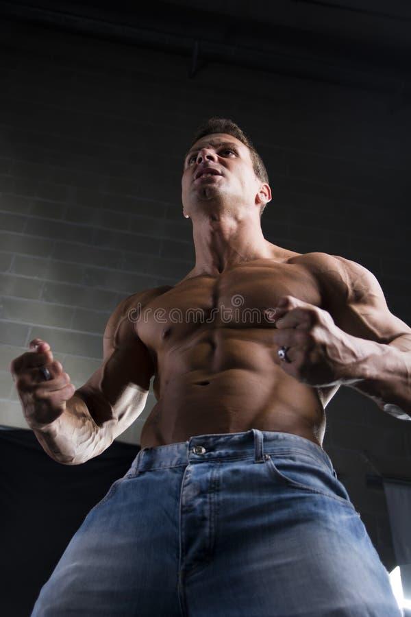 Starker junger Mann mit einer muskulösen Konstitution stockfotos