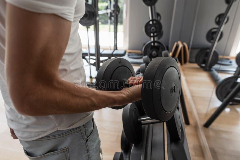 Starker junger muskulöser Mann, der in der Turnhalle ausarbeitet Nahaufnahme einer männlichen Hand mit einem Dummkopf stockfoto