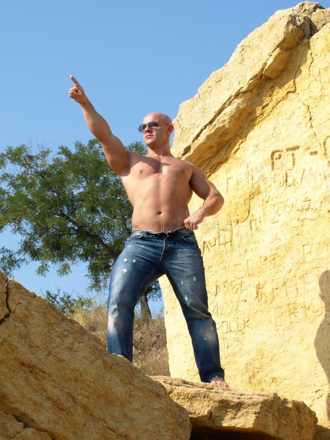 Starker kahler Mann, der oben zeigt lizenzfreie stockfotos