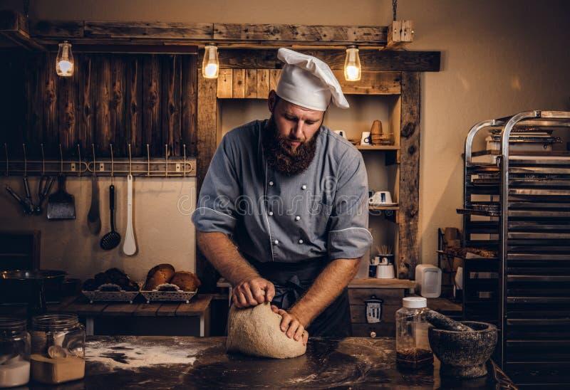 Starker knetender Teig des Chefs in der Küche stockbild