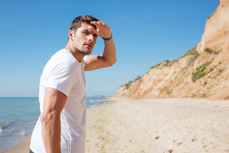 Starker Mann, der auf den Strand geht und weit weg schaut stockbild