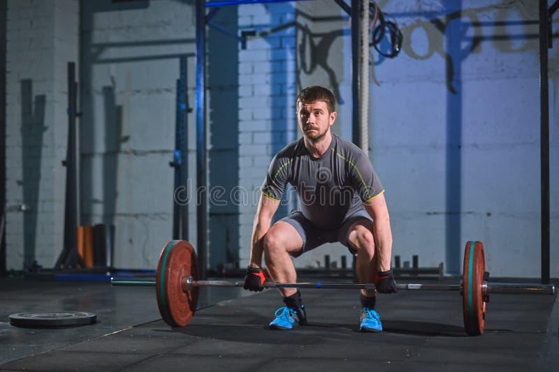 Starker Mann, der eine Übung mit einem Barbell in der Turnhalle auf einem Hintergrund einer grauen Betonmauer tut lizenzfreie stockfotografie