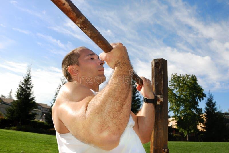 Starker Mann, der Pullups im Park tut lizenzfreies stockfoto