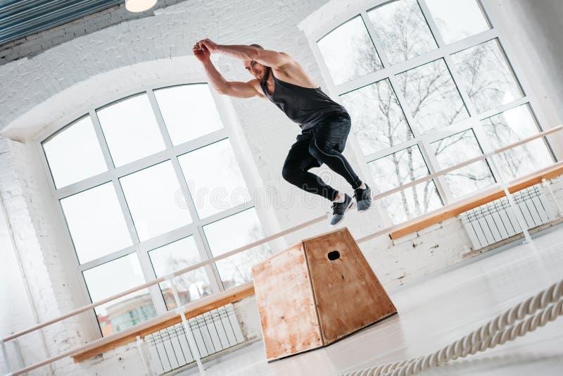 Starker Mann, der Sprung auf hölzernem untersetztem Kasten an der hellen Halle tut lizenzfreie stockfotos