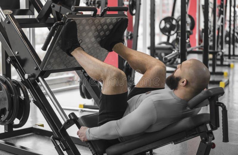 Starker Mann mit dem muskulösen Körper des Sitzes, der Übungen auf Beinpressemaschine, Training tut lizenzfreie stockbilder