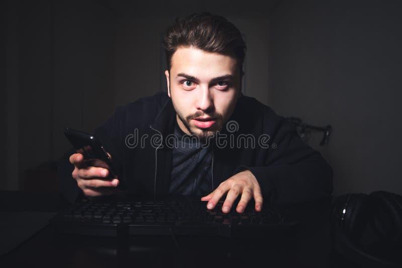 Starker Mann mit einem Bart und einem Smartphone in seinen Händen sitzt an der Nacht auf dem Computer und an den Blicken am Monit lizenzfreie stockfotos