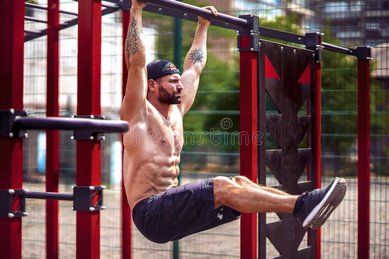 Starker muskulöser bärtiger Mann, der Abdominal- Übung auf horizontaler Stange im Sommerpark tut Eignung, Sport, trainierend lizenzfreies stockfoto