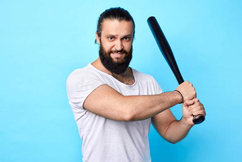 Starker muskulöser junger Mann, der Baseballschläger hält und geht zu treten stockbilder