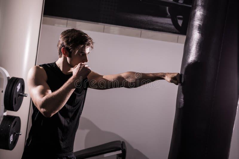 Starker muskulöser kickbox Kämpfer, der mit Sandsack auf Weiß in der Turnhalle trainiert lizenzfreie stockbilder