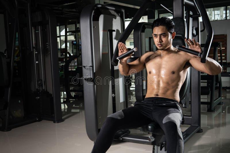 Starker muskulöser Mann, der für Training in crossfit Turnhalle sich vorbereitet Übendes Quersitztraining des jungen Athleten stockbild
