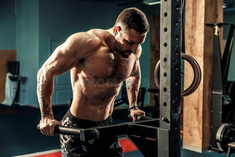 Starker muskulöser Mann, der StoßUPS auf Stufenbarren in crossfit Turnhalle tut lizenzfreies stockbild