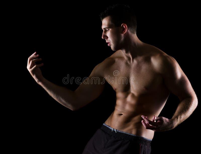 Starker muskulöser Mann, der würdevoll auf Schwarzem aufwirft lizenzfreies stockfoto