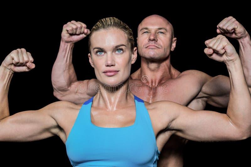 Starker muskulöser Mann und Frau, die Muskeln biegt lizenzfreie stockfotos