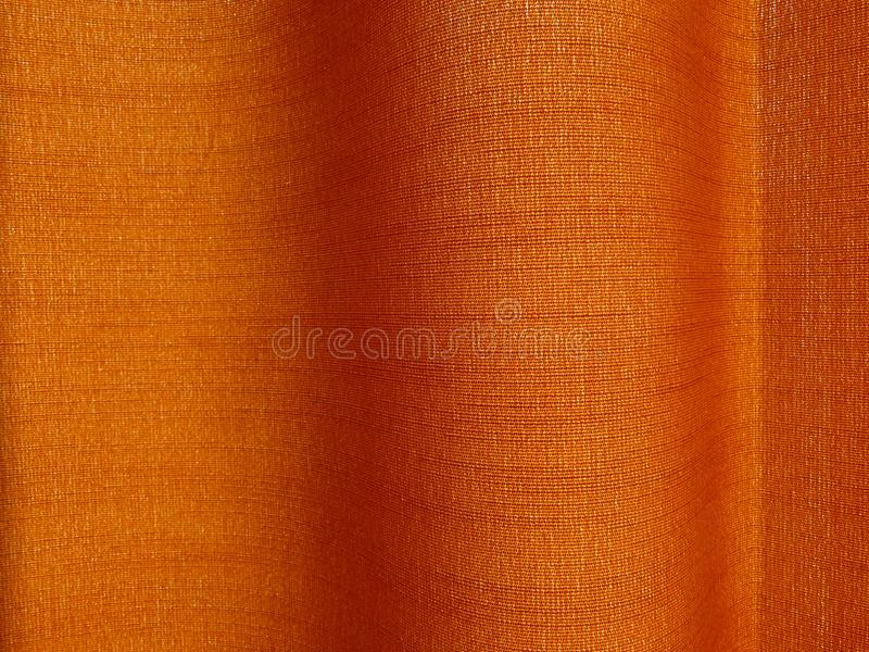 Starker Sonnenschein, der durch gesponnenes Textilstrukturiertes orange Farbvorhangdrapierung filtert stockbilder