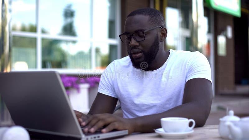 Starker Student, der an Hochschulprojekt unter Verwendung des Laptops, sitzend im Café arbeitet stockfotografie