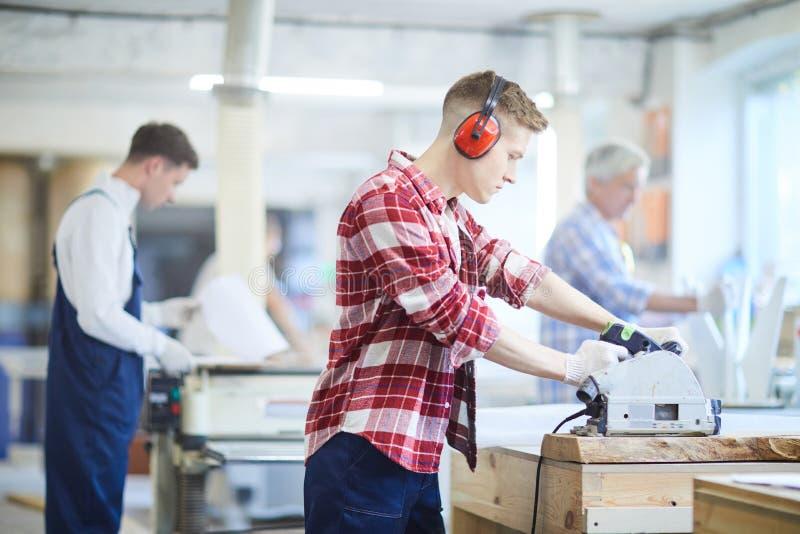 Starker Tischler in den Gehörschützern, die mit Kreiss arbeiten lizenzfreie stockfotos