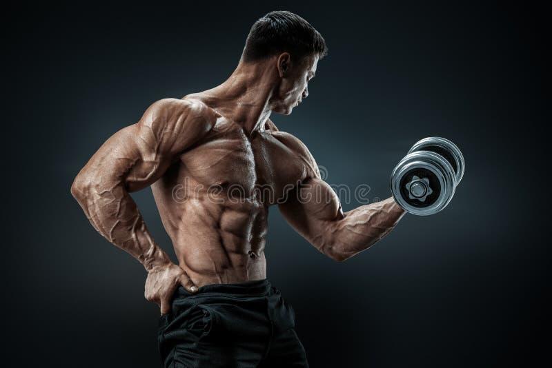 Starker und Machtbodybuilder, der Übungen mit Dummkopf tut stockfoto