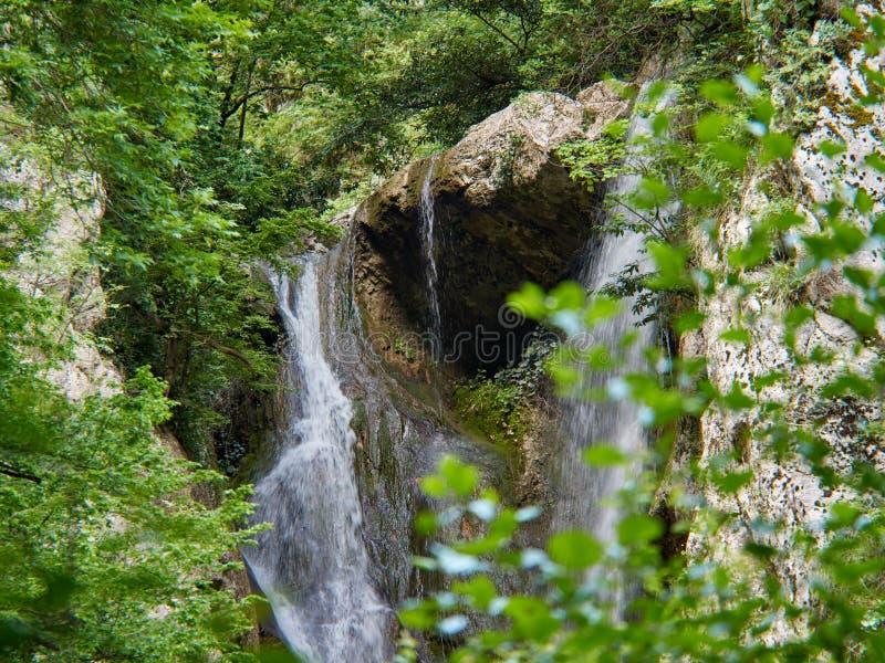 Starker Wasserfall fällt von den Klippen auf dem Frühlingsgebirgsfluss lizenzfreie stockfotografie