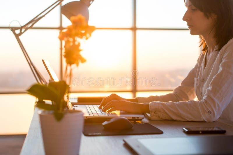 Starker weiblicher Angestellter, der am Arbeitsplatz unter Verwendung des Computers schreibt Seitenansichtporträt eines Werbetext lizenzfreie stockfotos