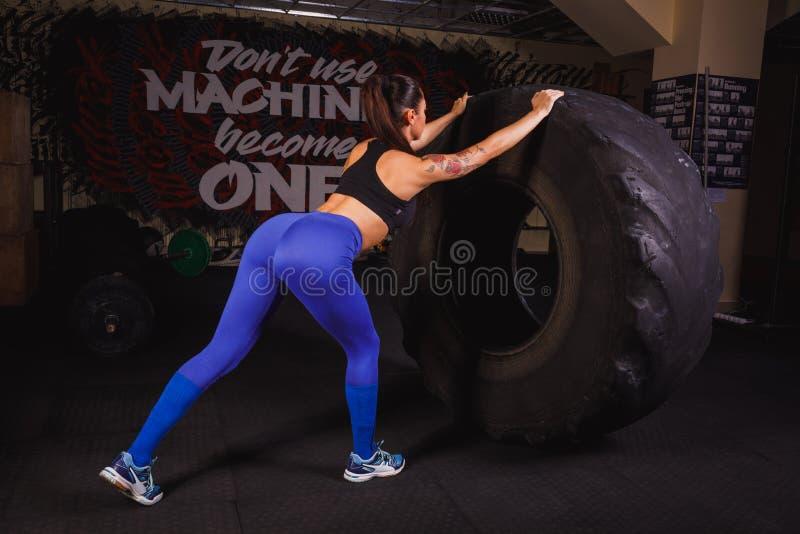 Starkes, attraktives muskulöses Mädchen engagierte sich im crossfit und bildete mit riesigen Reifen in der Turnhalle aus lizenzfreies stockfoto