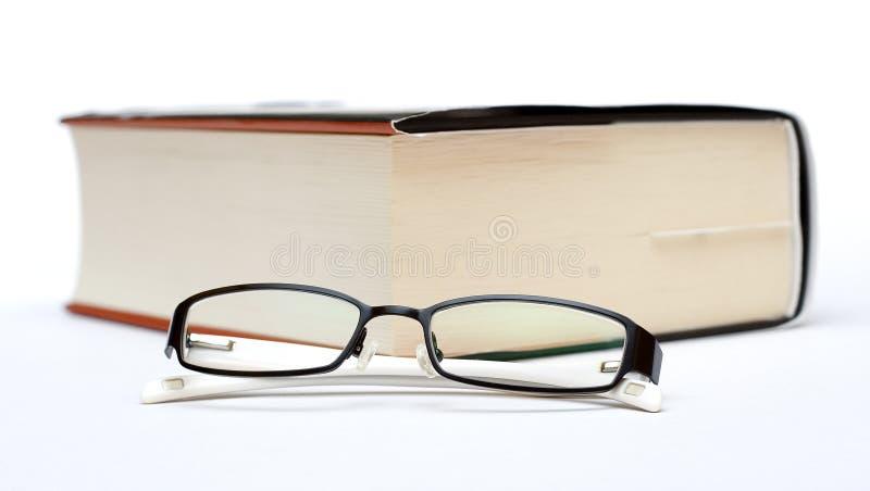 Starkes Buch und Gläser stockbilder