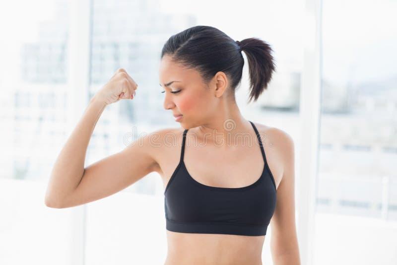 Starkes dunkelhaariges Modell in der Sportkleidung, die Vertrag ihrer Muskeln abschließt lizenzfreie stockfotografie