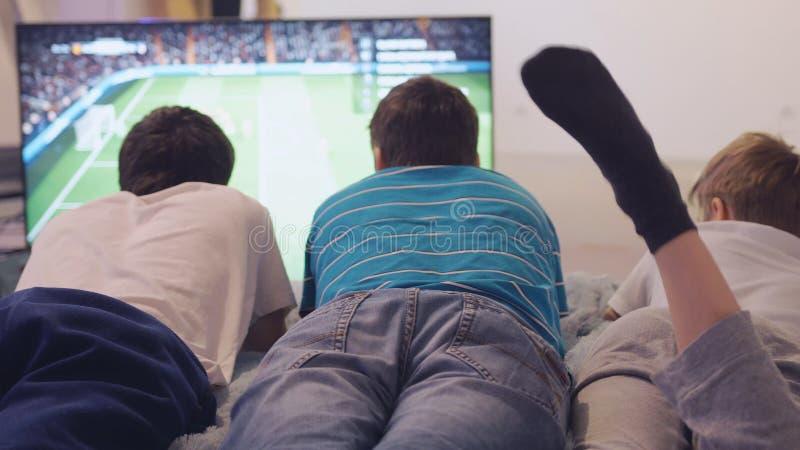 Starkes Fußballfan, das im Fernsehen ein Fußballspiel, aufpasst auf Sofa zu Hause zu liegen lizenzfreie stockfotografie