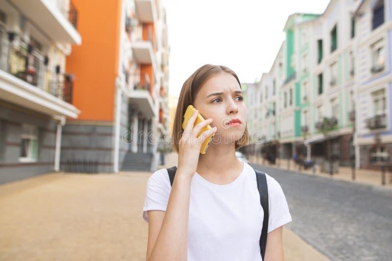 Starkes Mädchen in einem weißen T-Shirt, sprechend auf dem Smartphone auf der Straße und weg schauen stockfotografie