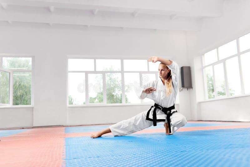 Starkes Mädchen, das im weißen Kimono mit übendem Karate des schwarzen Gürtels trägt stockbilder