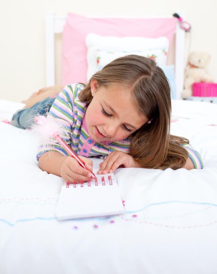 Starkes Schreiben des kleinen Mädchens auf einem Notizbuch lizenzfreies stockbild