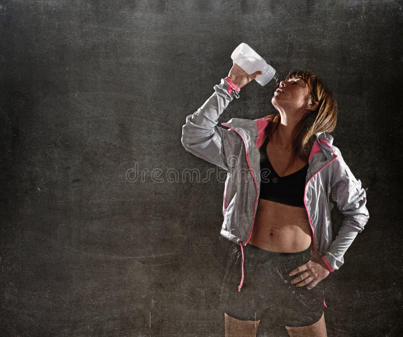 Starkt dricksvatten för sportfräknekvinna efter utbildande genomkörare i hårt ljus för idrottshallklubba royaltyfri fotografi