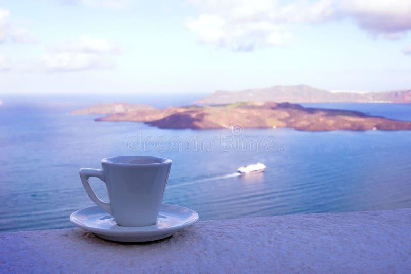 Starkt l?ckert kaffe i en vit kopp med ett tefat mot bakgrunden av havet och en sv?va eyeliner Stor start till dagen fotografering för bildbyråer