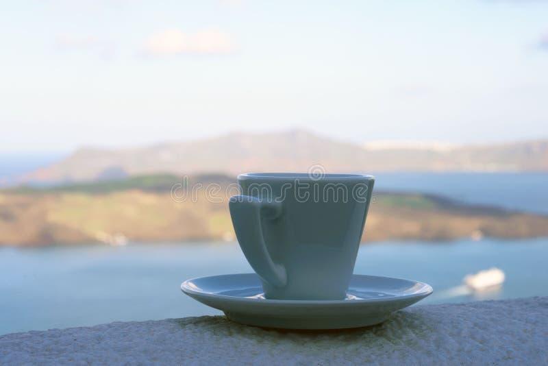 Starkt l?ckert kaffe i en vit kopp med ett tefat mot bakgrunden av havet och en sv?va eyeliner Stor start till dagen royaltyfri fotografi