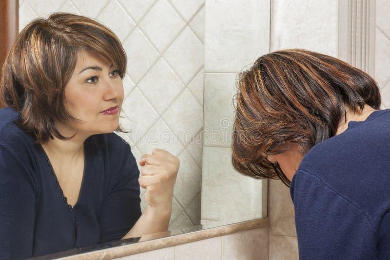 Starkt ledset se för kvinnaspegel royaltyfria foton