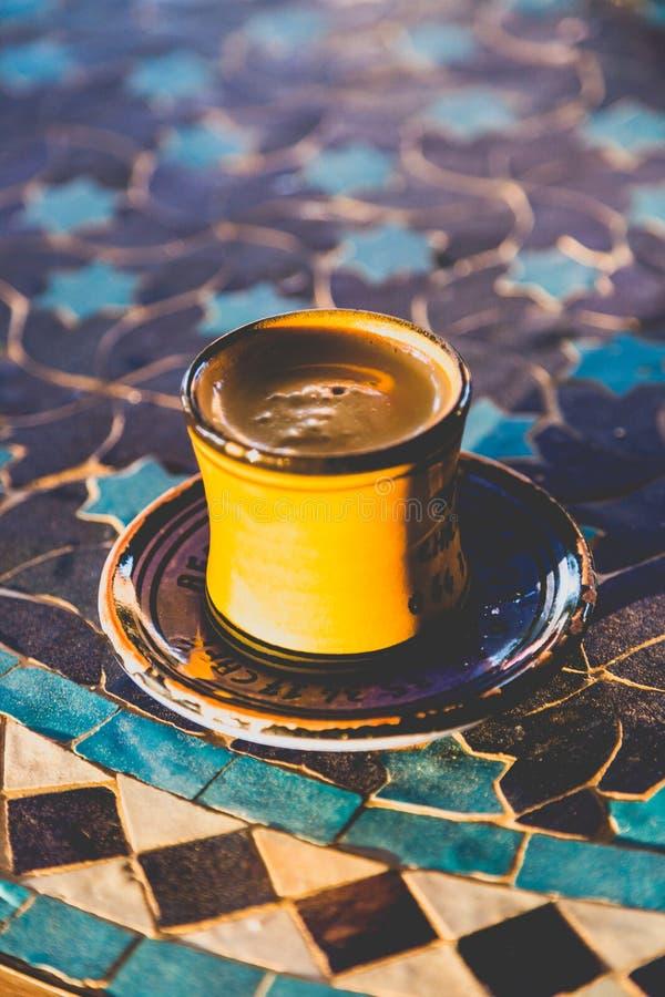 Starkt mörker grillade arabiskt kaffe i traditionell liten gul ce royaltyfria foton