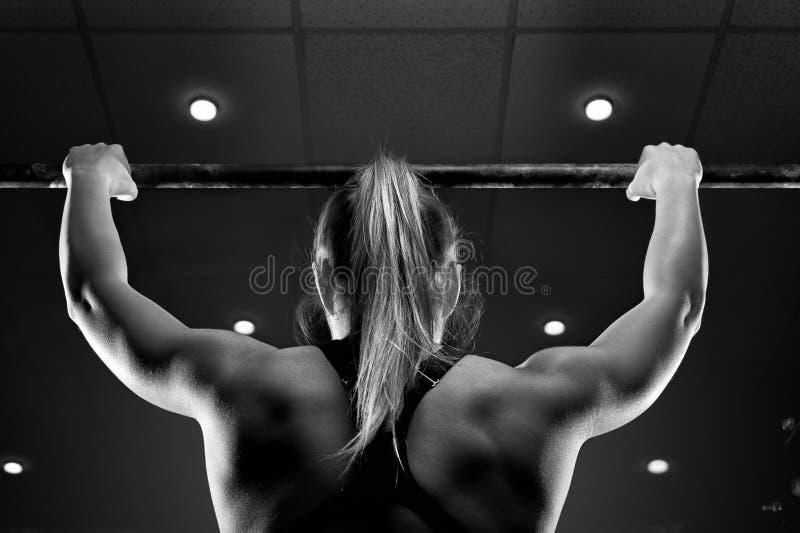 Starkt muskulöst kvinnligt görande handtag upp i idrottshall royaltyfri fotografi